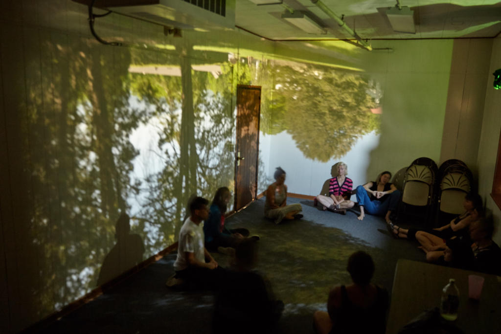 Students participating in sonic meditation in during an experimental music class sitting in a classroom-sized camera obscura made by another class. Photo by Suzi Sadler
